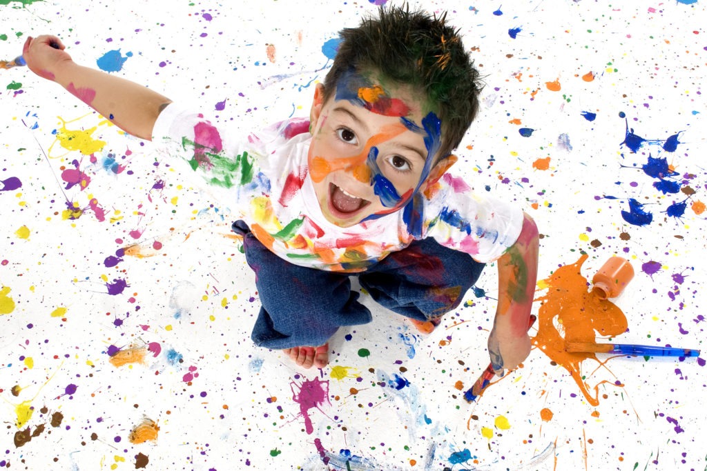 Adorable 3 year old boy covered in bright paint. Full body shot from above.